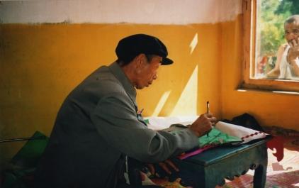Li Manshan doing paperwork for Hoisting the Pennant ritual, 2003 https://stephenjones.blog/the-film/