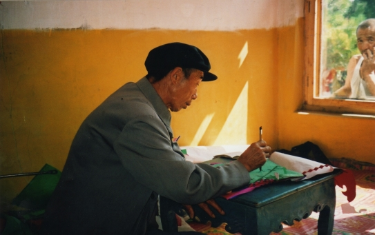 Li Manshan doing ritual paperwork, 2003